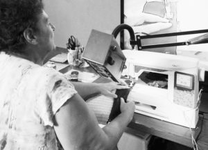 Vera working with her sewing machine and magnification