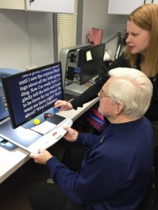Client being shown video magnifier by optometrist